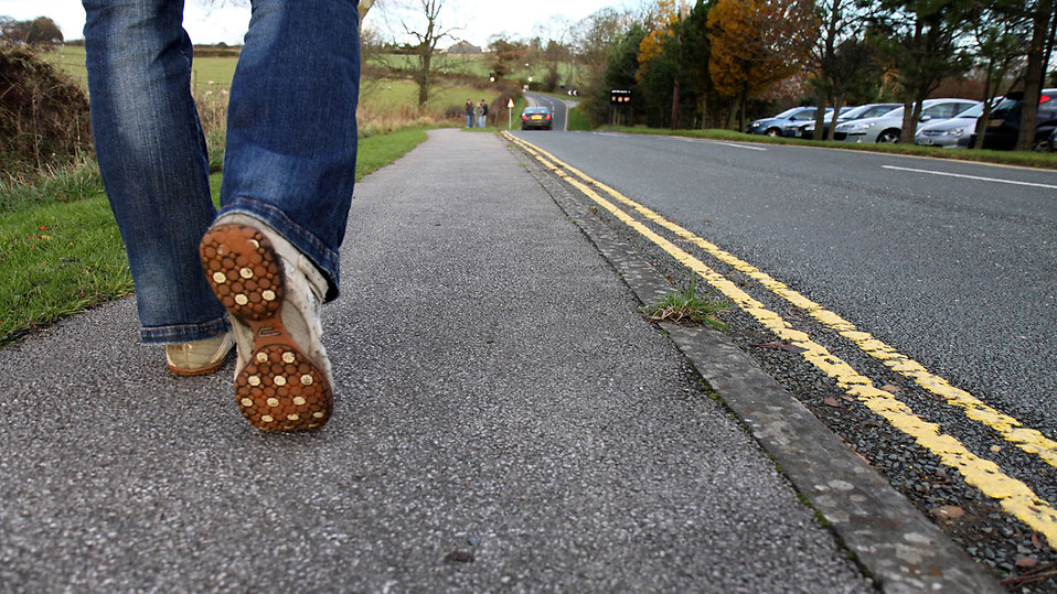 close-up-of-feet-walking-on-a-road-pv